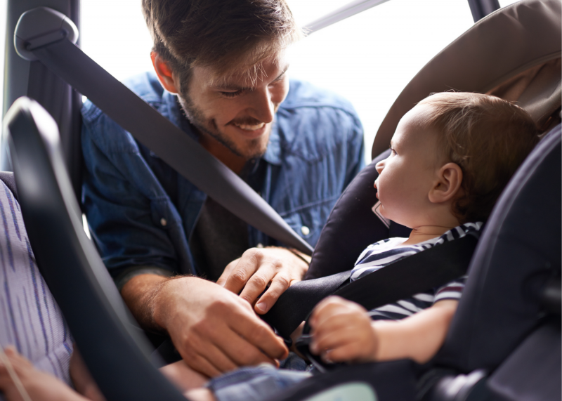 Dad taking baby out of car restraint