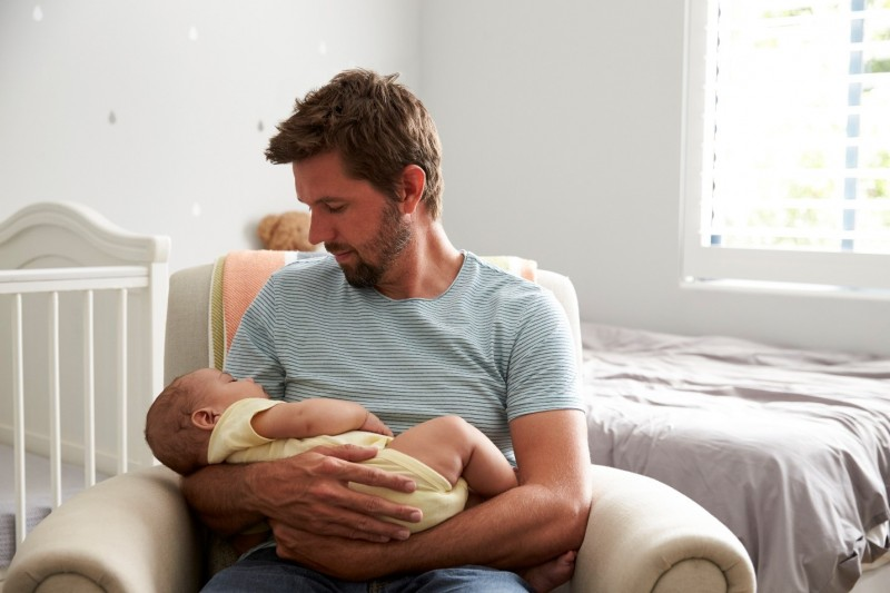 Dad holding baby in nursery