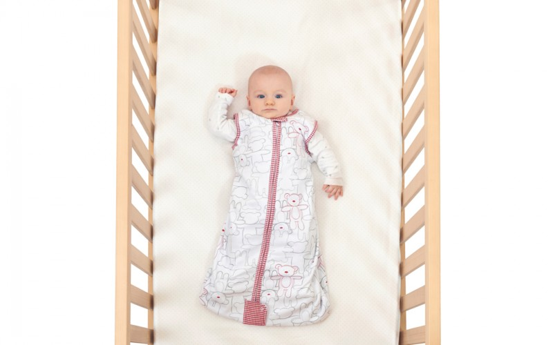 Baby in cot image for mattress wrapping article